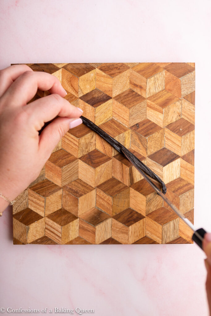 hand holding a vanilla bean lengthwise and slicing it in half on a wood board on a light pink surface