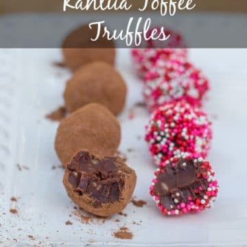 kahlua toffee truffles rolled in cocoa powder and sprinkles on a white plate on a wood board
