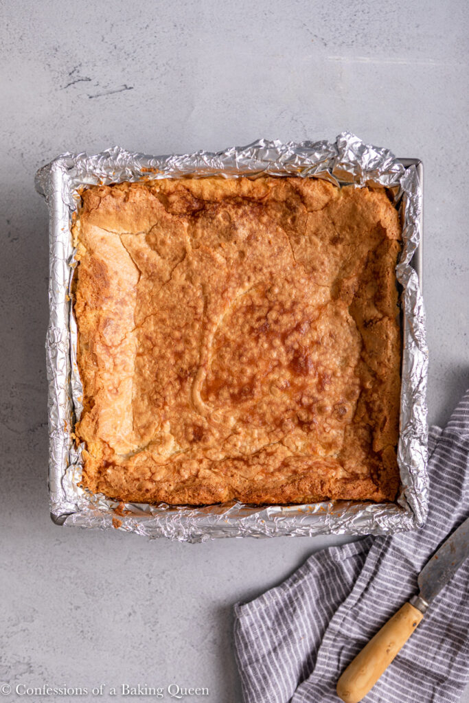 ooey gooey butter bars just out of the oven on a light grey surface with a linen and knife