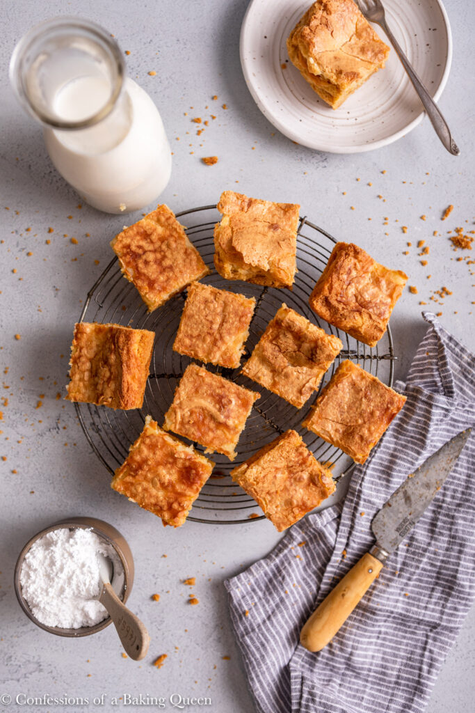 ooey gooey butter bars on a wire rack with a glass of milk, bowl of sugar, plate, knife and linen on a light grey surface