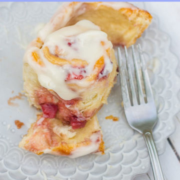strawberry sweet roll with glaze being eaten with a silver fork on a purple plate