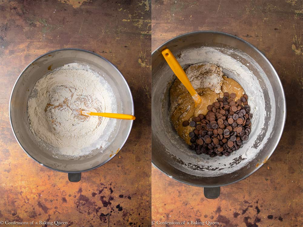 chocolate chips and flour folded into wet ingredients in a metal bowl for chocolate chip cookie dough in a metal mixing bowl with an orange spatula on an orange and brown distressed surface