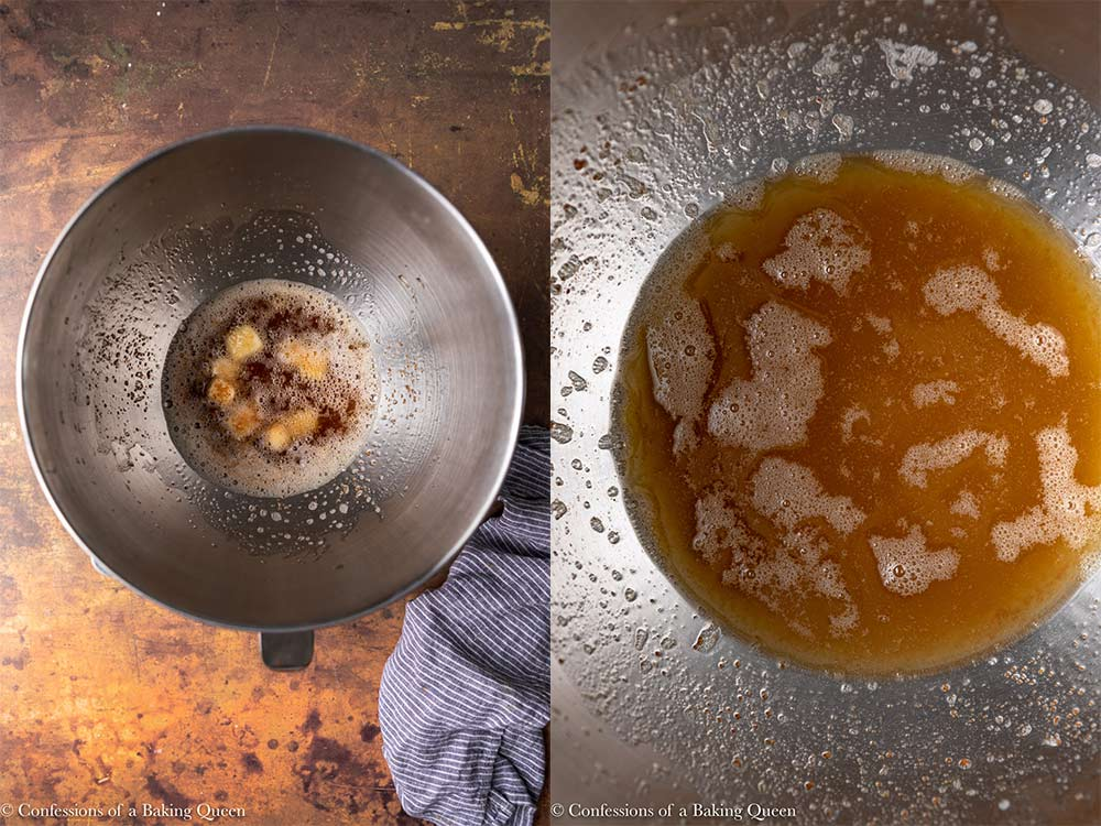brown butter poured on top of cubbed butter in a metal mixing bowl with a navy blue linen next to it on a distressed brown-orange surface