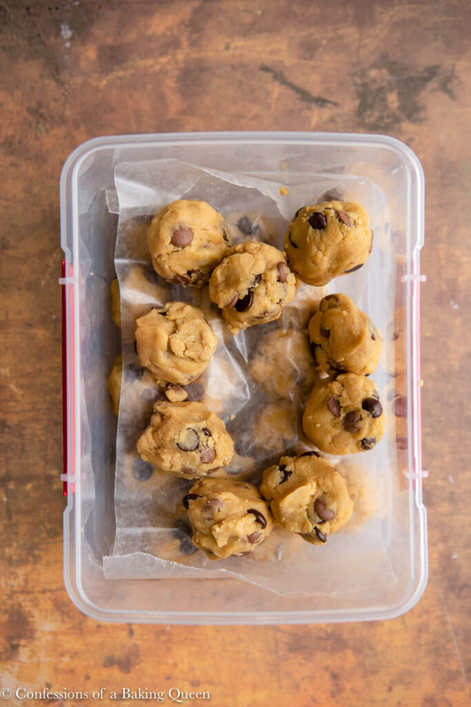 chocolate chip cookie dough balls layered in between wax paper in a plastic container sitting on a brown and orange distressed surface