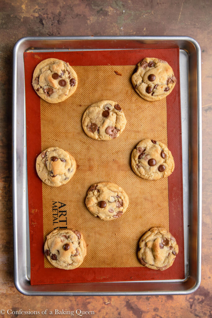 chocolate chunk cookies just baked on a silpat lined baking sheet sitting on an orange and brown distrssed surface