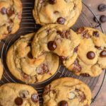 close up of easy chocolate chip cookies on a wire rack on a brown and orange distressed surface next to a blue linen and a dark bowl with chocolate chips spilled out