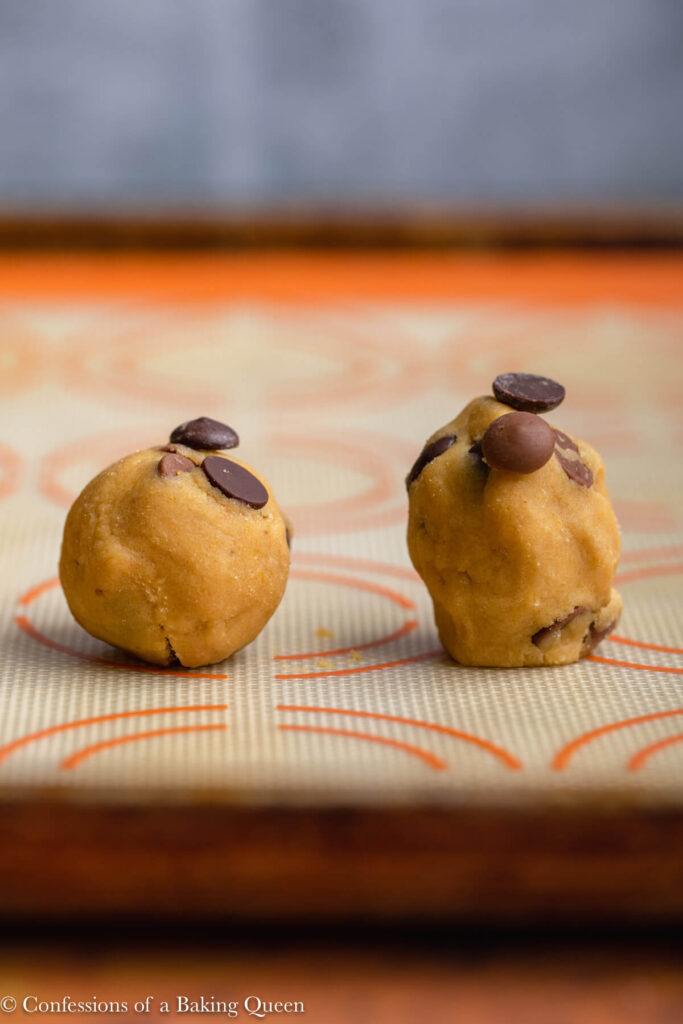 close up of two chocolate chip cookie dough balls on a silpat lined baking sheet