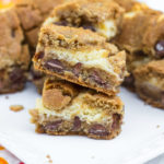 Cookie Butter Chocolate Chip Cheesecake Bars stacked on top of each other on a white plate on a white wooden background