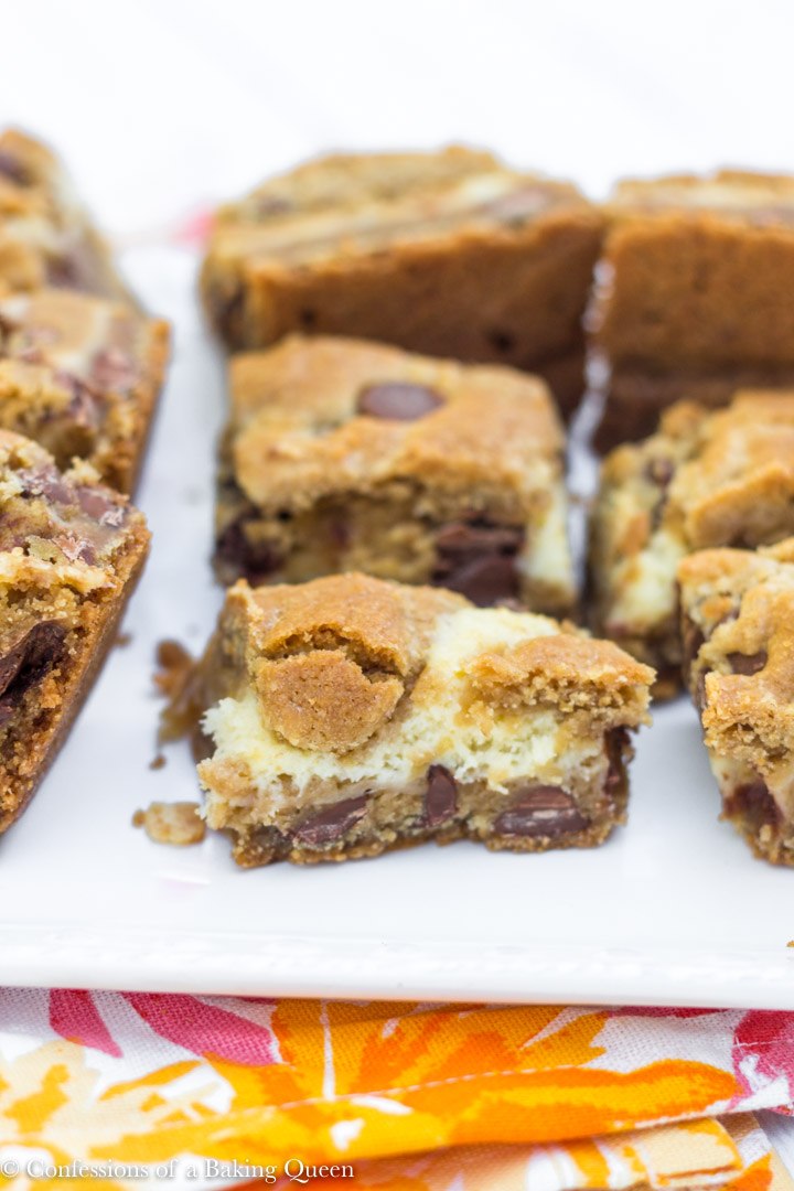 Cookie Butter Chocolate Chip Cheesecake Bars lined up on a white plate