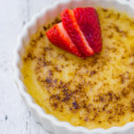 lemon creme brulee in a white ramekin with sliced strawberries on top