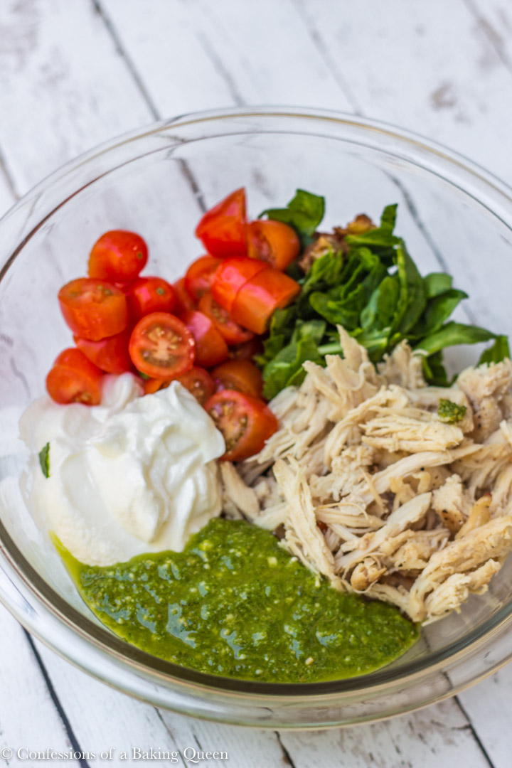 ingredients for a lightened up pesto chicken salad in a large clear bowl