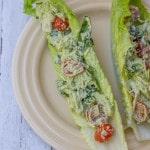 Pesto Chicken Salad on lettuce on a tan plate