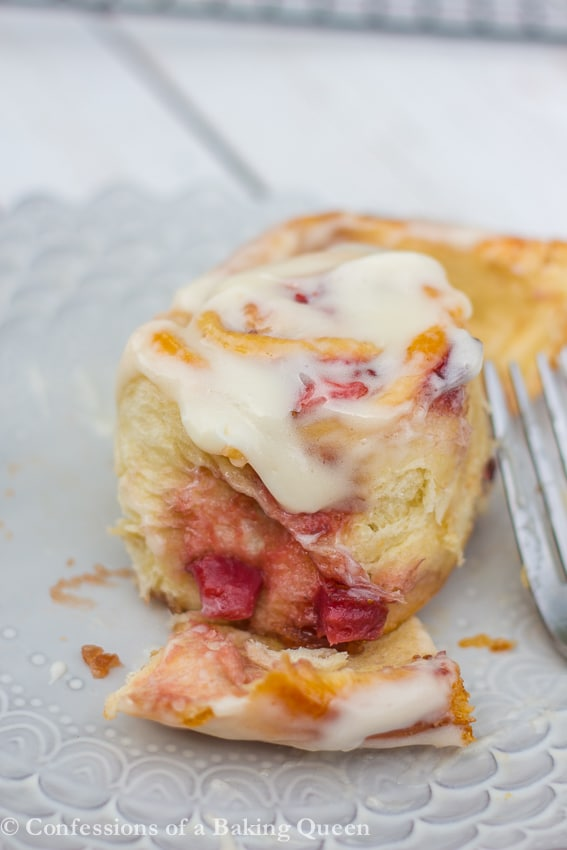 homemade strawberry sweet roll opened up on a purple plate with a white background