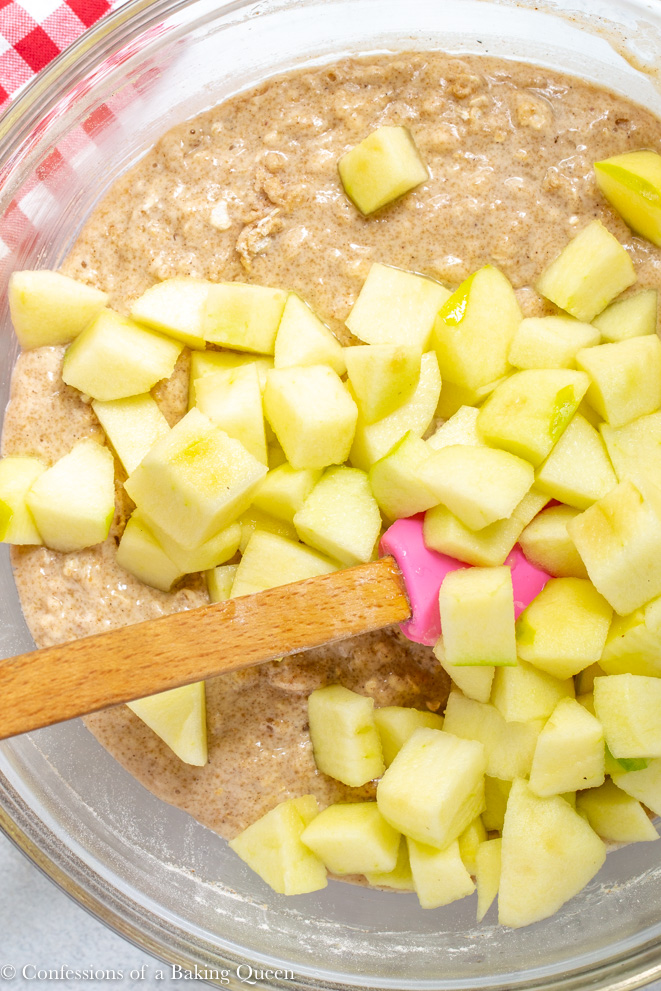 apple chunks added to maple apple bread recipe in a large clear bowl with a pink spatula to mix them in on a white counter next to a red linen