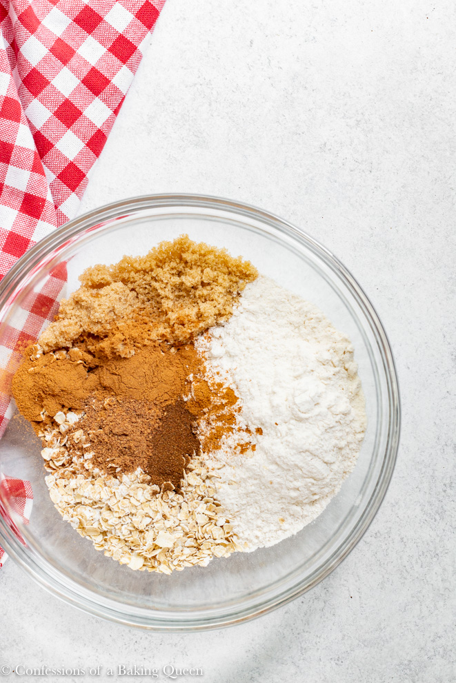 crumble topping ingredients in a clear bowl on a white counter with a red and white napkin
