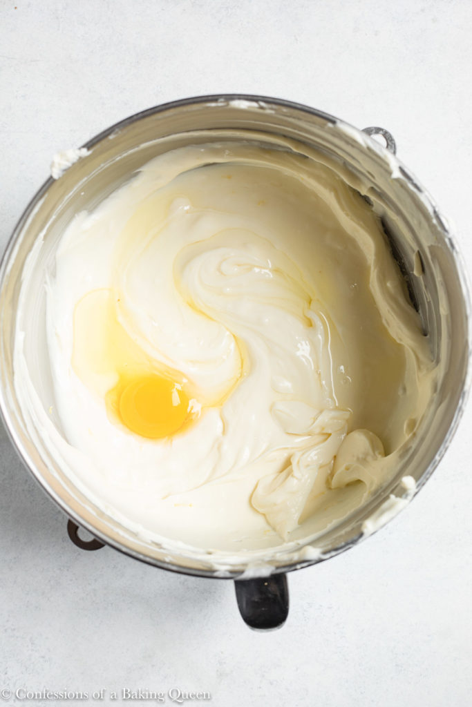 egg added to cheesecake batter in a metal bowl
