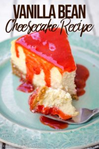 slice of vanilla bean cheesecake with strawberry sauce on a turquoise plate