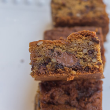 salted caramel pecan chocolate chip blondies stacked on top of each other on a white plate