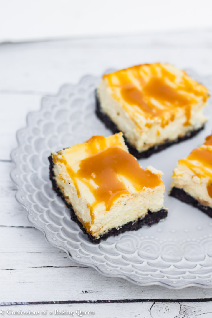 three caramel cheesecake bars on a purple plate on a white wood background
