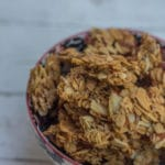 Maple Almond Granola Clusters baked and served in a white, black and pink bowl on a white background