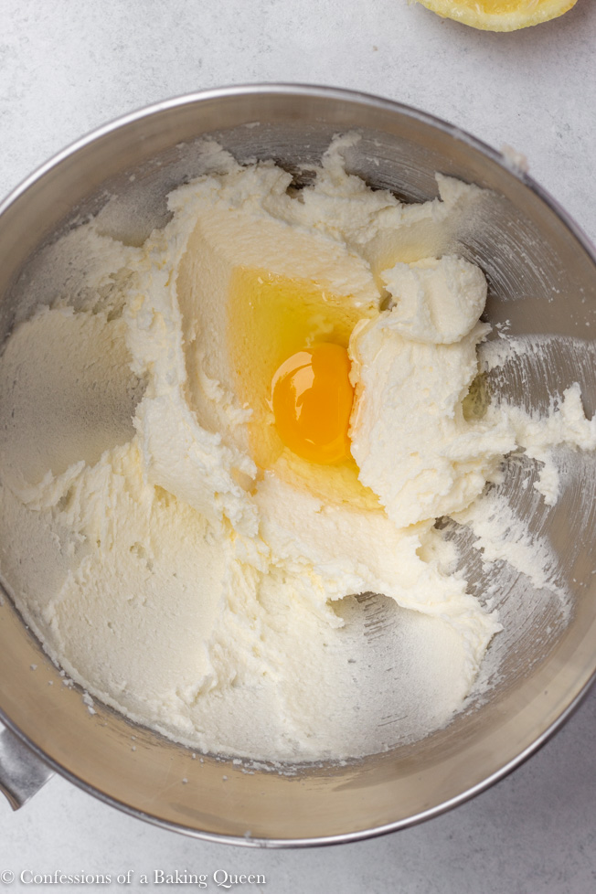 egg being added to creamed sugar and butter in a silver bowl for raspberry lemon loaf cake