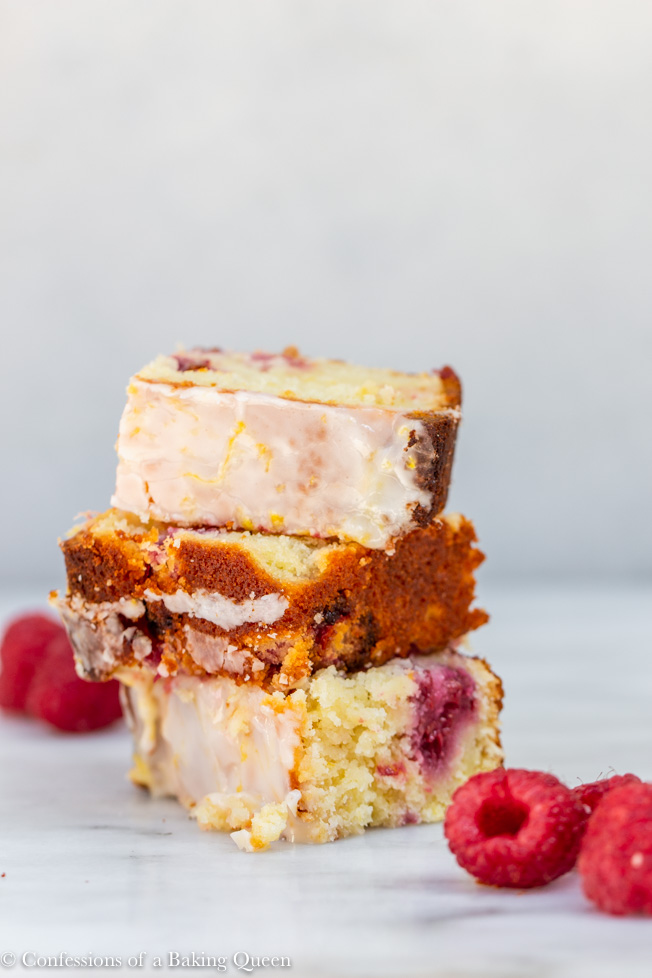 raspberry lemon loaf cake pieces stacked on top of each other with raspberries on a white marble surface