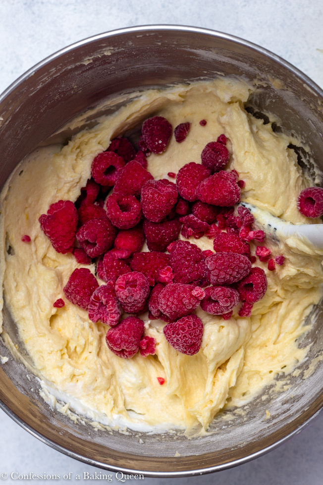 raspberries being added to cake batter in silver bowl for raspberry lemon loaf cake on a light grey/ white background