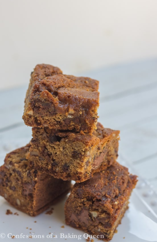 Salted Caramel Pecan Chocolate Chip Blondies stacked on top of each other on a white plate on a white background