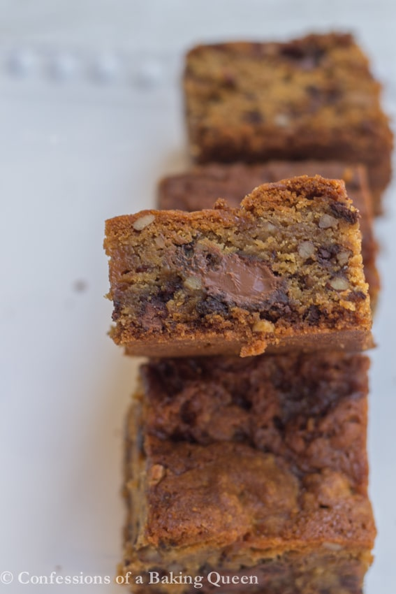 Salted Caramel Pecan Chocolate Chip Blondies side shot with gooey chocolate on a white plate