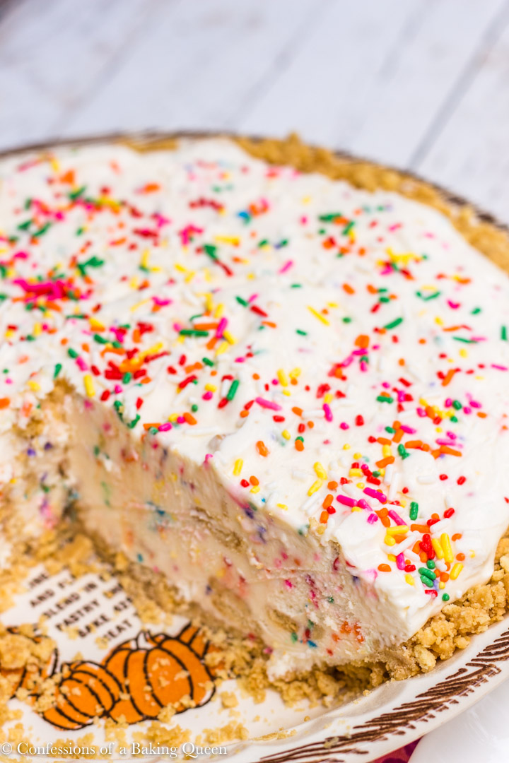 golden oreo cake batter ice cream pie in a white and brown pie dish