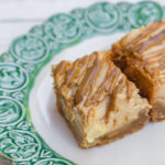 Biscoff Apple Cheesecake Bars on a white plate with green rim on a white background