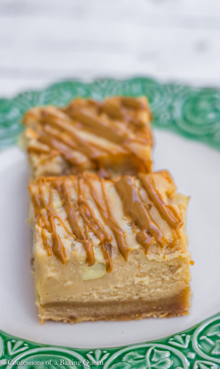 biscoff apple cheesecake bars lined up on a white and green plate on a white background