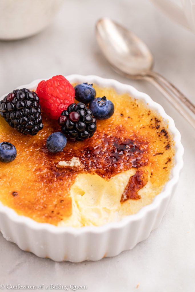 creme brulee missing a few bites with fresh berries on top on a white marble surface