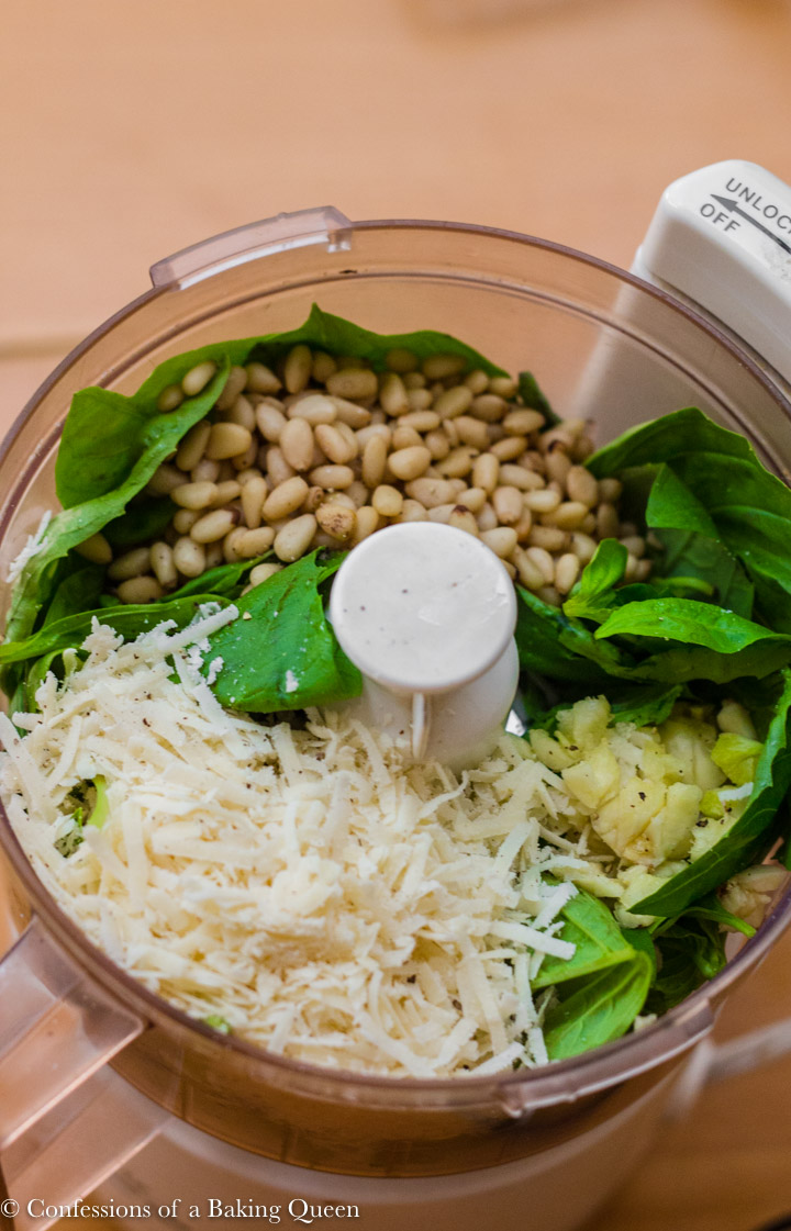classic basil pesto ingredients in a food processor on a wood table