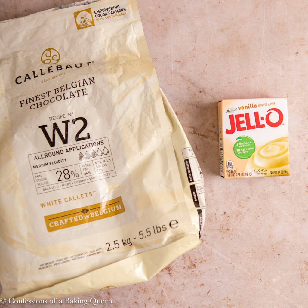 callebaut white chocolate callets and a box of vanilla pudding mix on a light brown surface