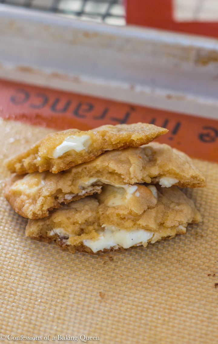 chewy white chocolate cookies broken in half stacked on top of each other on a silpat lined baking sheet