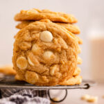 close up of a cookie standing up on a wire rack on top of a blue stripped linen on a light brown surface