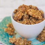 Cookie Butter Granola in a white cup on a blue plate