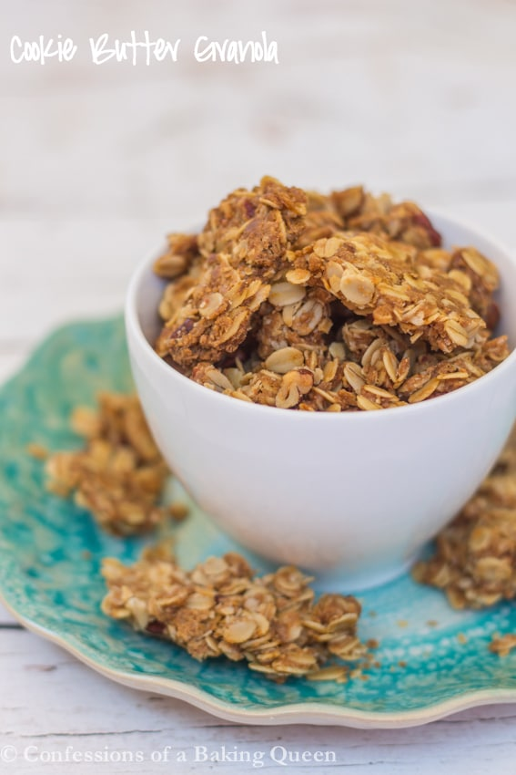 cookie Butter Granola in a white cup on a blue plate overflowing on top of a white background
