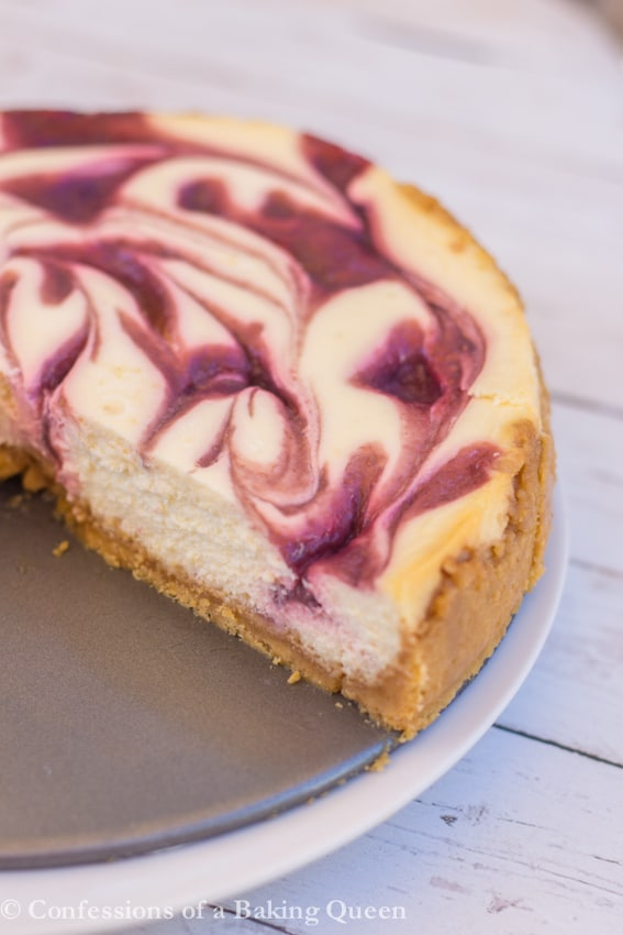 Raspberry Puree is swirled through a luscious lemon cheesecake all on top of a Lemon Golden Oreo Crust make this Raspberry Lemon Cheesecake irresistible www.confessionsofabakingqueen.com