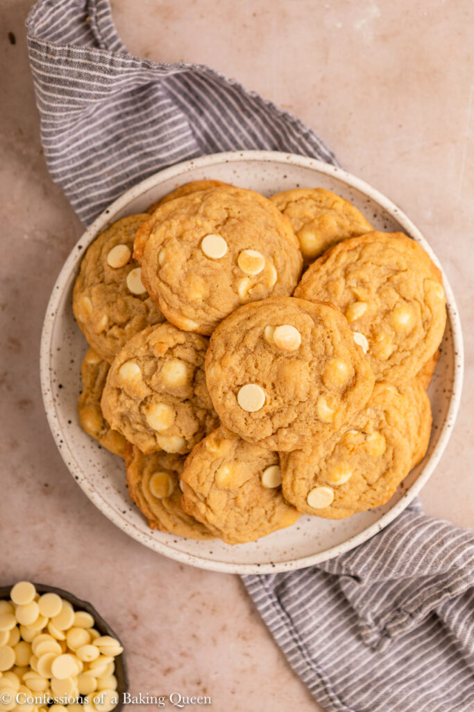 plate of white chocolate chip cookies on a plate on top of a blue linen on a light brown surface