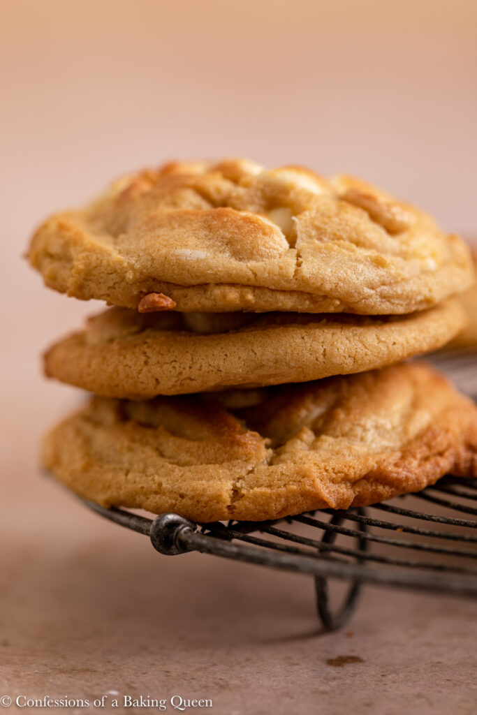 stack of three white chocolate chip cookies on a wire rack on a light brown surface