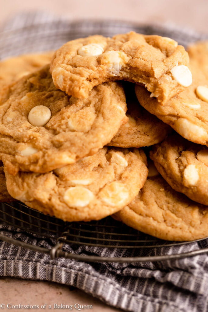stack of white chocolate cookies and the top cookie missing a bite on top of a blue stripped linen on a light brown surface