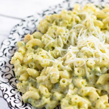Pesto Chicken Mac & Cheese on a black and white plate on a white background