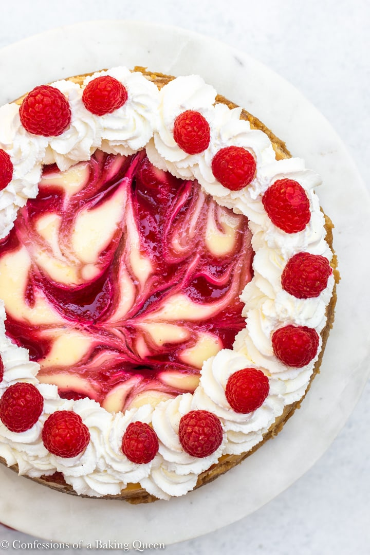overhead shot of a raspberry swirl lemon cheesecake on a white cake stand on a white surface