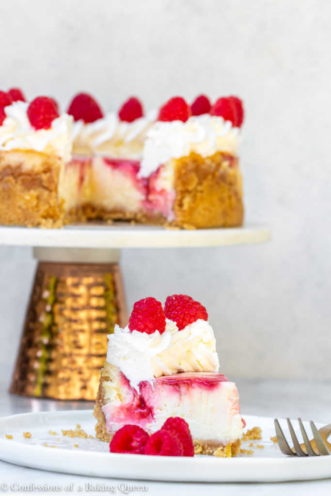 rraspberry swirl lemon cheesecake slice on a white plate with the full cheesecake on a stand in the background on a white surface