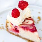 close up of raspberry swirl lemon cheesecake on a white plate