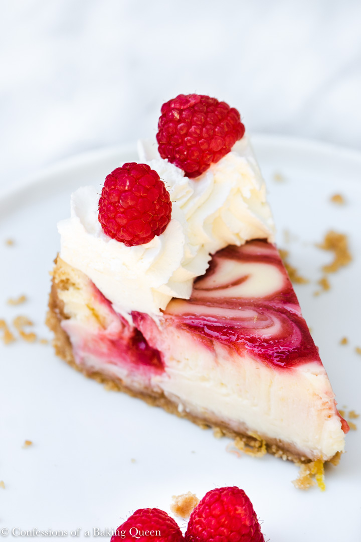 close up of raspberry swirl lemon cheesecake on a white plate on a white surface
