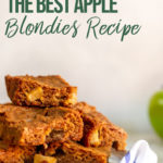 apple blondies stacked high on a white plate on a white marble background
