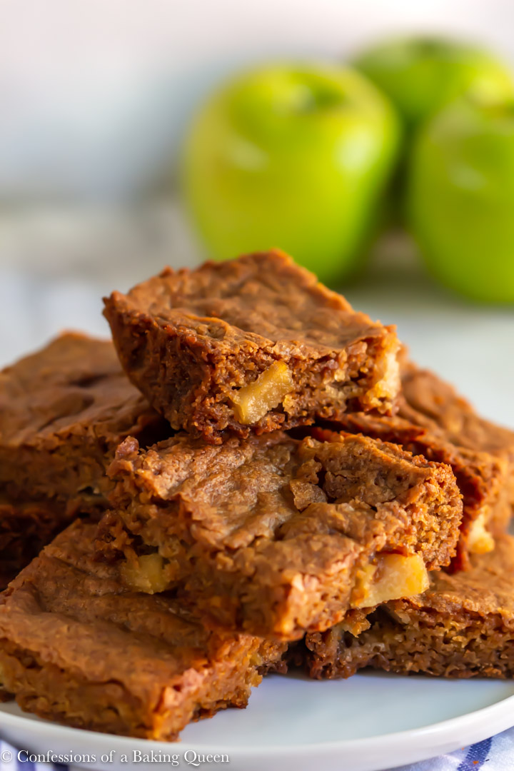 close up of apple blondies stacked high on a white plate on a white marble background